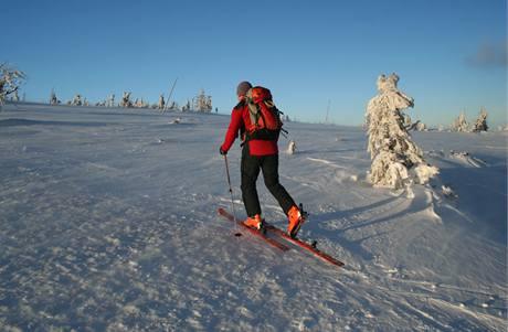 """Při cestě vzhůru je skialpové vázání přepnuté na """"volnou patu"""" a na lyžích jsou zespoda připnuté pásy proti klouzání zpět."""