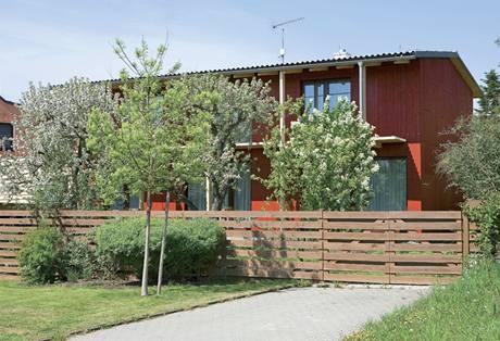 Dům díky červené dřevěné fasádě a také díky zastiňovacím prvkům působí lehce a vzdušně