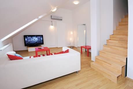 K odpočinku v obývacím pokoji slouží pohovka Klippan a barevné odkladní stolky(vše IKEA)