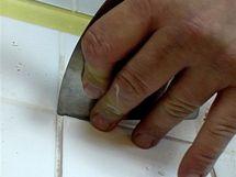 Špachtli držte za spodní konec, aby nevyjela ze spáry a nepoškodila vedlejší obklad