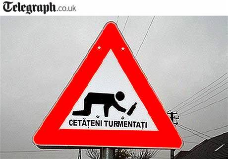 Dopravní značka v Rumunsku varuje řidiče před opilými chodci.