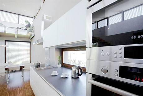 Kuchyňská část je vybavena střídmou linkou z bíle lakovaných MDF desek s vysokým leskem, pracovní deska je šedá