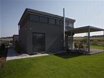 Společná obytná část domu převyšuje ostatní funkční celky a je navenek odlišena tmavě šedou omítkou