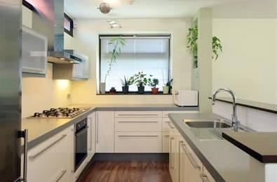 Kuchyňskou linku architekti navrhli z lakovaných MDF desek v neutrální nadčasové kombinaci antracitové a bílého laku