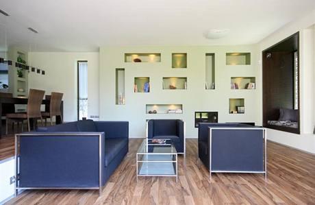 Knihovnu nahrazuje vyzděná obývací stěna s osvětlenými nikami