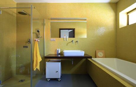 Střídmý design koupelny rodičů je založen na kontrastu velkoformátové dlažby a jemné mozaiky, šedé a žluté barvy