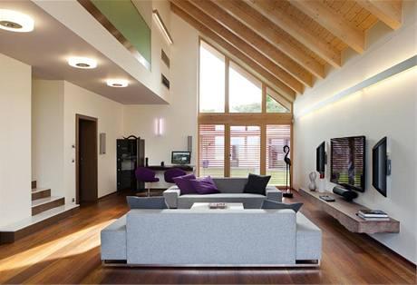 Společný obývací prostor přesahuje do horního podlaží, z otevřené galerie se otevírá výhled do pokoje i ven do krajiny. Nábytku tu najdeme jen málo, dominantní je výhled. K zastínění oken i jako tepelná izolace slouží venkovní žaluzie