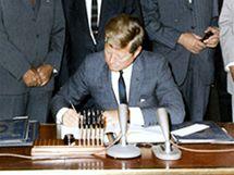 John Fitzgerald Kennedy podepisuje smlouvu v roce 1963 v Bílém Domě v USA.