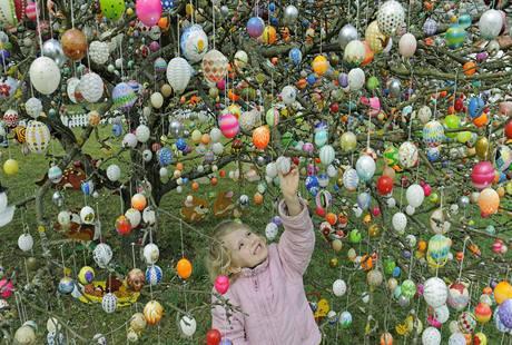 Holčička v Německu si prohlíží velikonoční strom ozdobený stovkami kraslic