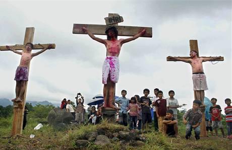 Indonéské děti si prohlížejí ukřižované věřící