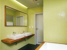 Koupelna v patře. Umyvadlový pult je vyroben z teakového dřeva stejně jako obložení vany. Zrcadlové skříňky architekt navrhl zapustit do zdi.