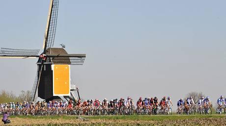 Cyklisté na trati závodu Amstel Gold race míjejí větrný mlýn.