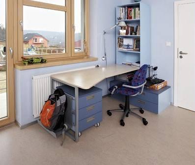 Pracovní stůl je vybaven pojízdným kontejnerem. Široké okno propouští na pracovní plochu dostatek světla.