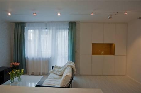 V celém pokoji najdete pouze dva barevné prvky - zelené závěsy a dřevěnou niku