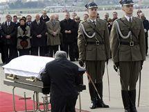 Bratr zesnulého prezidenta Jaroslaw Kaczynski klečí na varšavském letišti před rakví. (11.4. 2010)