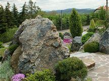 Některé ozeleněné kamenné partie se přímo před domem zvedají přímo z plochy terasy, zatímco v trávníku jsou velké balvany usazené v ostrůvcích kamenné drti.