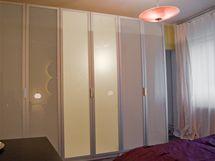 Šatní skříně zabírají celou jednu stěnu, mezi nimi a oknem jsou nové dveře do obýváku