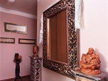 Pohled z ložnice na zarámované tibetské svitky s motlitbami v pozadí