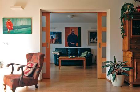 Průhled z obývacího pokoje do místnosti s akváriem. Bambusová podlaha volně probíhá a opticky zvětšuje prostor