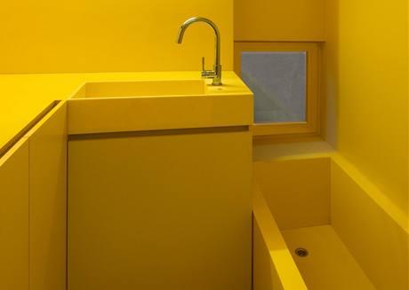 Stěny v koupelně jsou vymalovány omyvatelnou barvou ve žlutém odstínu. Vana je z moderního materiálu Corian