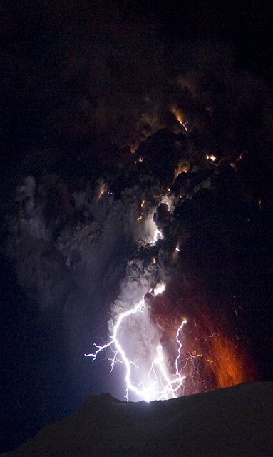 Islandská sopka Eyjafjallajökull chrlí lávu, v mraku sopečného popela se kříží blesky. (20. dubna 2010)
