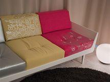 Polštáře na sedačce jsou potažené stejnou látkou, ale ve třech barvách. Ty se opakují i na jídelních židlích.