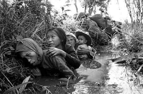 Vietnamské ženy a děti se v lednu 1966 krčí v bahnitém kanálu poblíž Bao Trai, schovávají se před těžkou palbou Vietkongu.