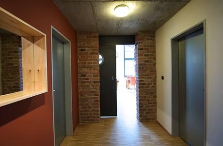 Cihlová barva v chodbě příjemně doplňuje šedou na dveřích a zárubních