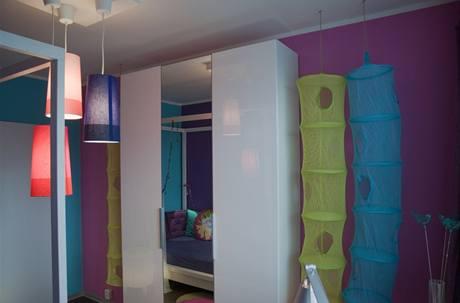 Prostor je laděný do tří barev:  fialové, modré a růžové, doplňuje jej nadčasový bílý nábytek