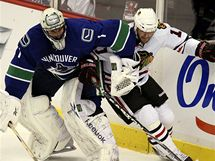 John Madden z Chicaga v souboji s brankářem Vancouveru Robertem Luongem.