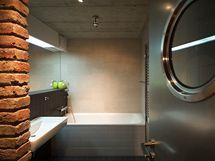 Koupelnu opticky zvětšuje velké zrcdalo na zdi