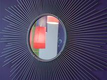 Prostor nad postelí zdobí zrcadlo ve tvaru slunce