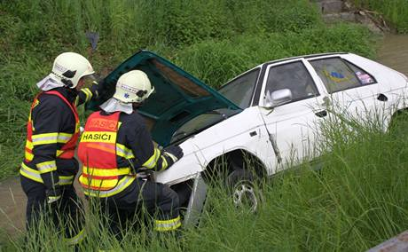Auto skončilo v potoce střechou dolů, obyvatelům Bohuslavic se podařilo zachránit posádku a otočit jej na bok. (14. května 2010)