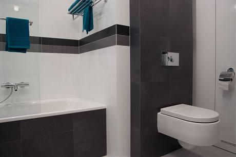 Koupelna je v módní bílé a šedé barvě