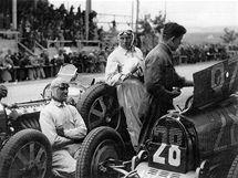 Louis Chiron se nahřívá u motoru Bugatky a přihlíží práci mechanika u svého vozu Bugatti č. 28. (r.1931)