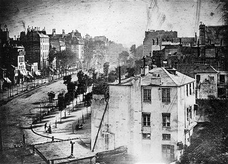 """Boulevard du Temple, Paříž v roce 1838 - první snímek člověka. Zdánlivě klidná ulice byla ve skutečnosti rušnou třídou. Dlouhá expozice (více než deset minut) však """"vymazala"""" všechno, co se hýbalo. Na snímku zůstal pouze muž, který si nechává čistit boty."""