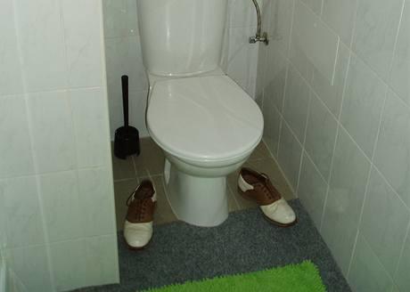 Aby se koberec na toaletě neroloval, zatížil jej majitel starými botami na golf