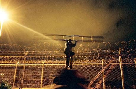 Kamerunský uprchlík se pomocí dvou žebříků snaží dostat přes hraniční plot mezi Marokem a Španělskem.