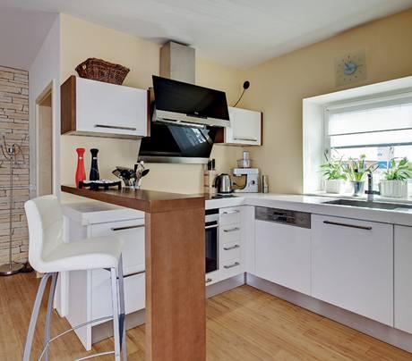 Bílou kuchyňskou linku od firmy Koryna nábytek odděluje od zbytku obývací místnosti barový pult