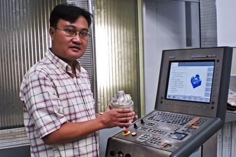 Major Sai Thein Win stojí na fotografii z prosince 2009 u zařízení, které je součástí jaderného výzkumu