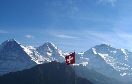 Švýcarsko. Pohled na trio Eiger, Monch, Jungfrau ze Schynigge Platte (za vlajkou observatoř Sphinx)
