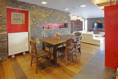 Ráz obývacího pokoje udává dominantní kamenné obložení obvodového zdiva. Niky jsou upraveny červeným benátským štukem