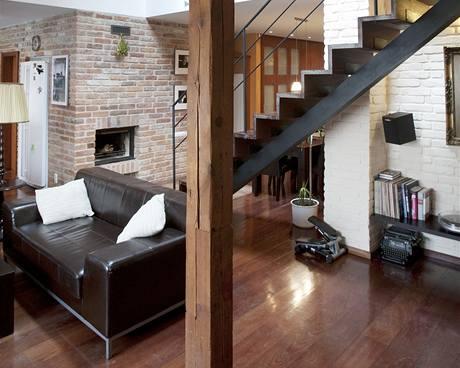 Dřevěné schodiště s kovovým zábradlím spojující přízemí s patrem nepůsobí v interiéru rušivě