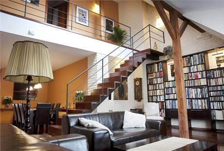 Obývacímu pokoji dominuje knihovna, která zabírá celou jednu stěnu místnosti