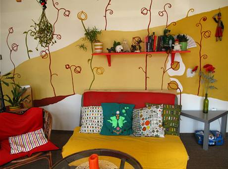 Protože stěna působila po pomalování trochu moc prázdně, natřeli starou polici na červeno a zavěsili ji nad gauč