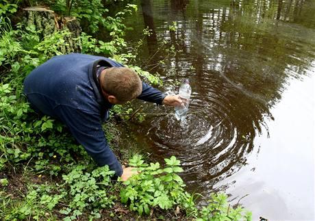 Rybář Radek Hylmar kontroluje stav vody v rybnících, které někdo obarvil načerveno.