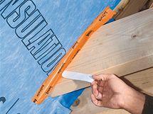Z oranžové lepicí pásky kus odřízneme, stáhneme nejdříve jen polovinu ochranné fólie ze zadní strany a lepicí plochu přitlačíme na okraj fólie. Pak stáhneme druhou polovinu ochranné fólie a lepicí plochu přitlačíme na dřevo