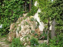 Travertinov� skalka ukryt� za rohem domu.