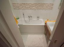 Stěny jsou obložené bílými kalibrovanými dlaždicemi 30 x 60 cm kladenými jen s malou spárou, stěnu zdobí opět kámen