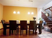 Jídelní kout s mohutným obdélníkovým stolem a pohodlnými koženými křesly je přímo před vchodem do bytu